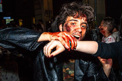 Vampire bites a prey. Bologna, Italy - May 21, 2016: Bologna zombie apocalypse walk: closeup of a vampire biting the arm of a victim Stock Photo