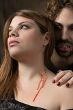 Vampire bites woman. Man vampire bites the neck of a woman Stock Photo