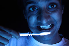 Vampire Brush his Teeth. An Indian vampire brushing his teeth with a white toothbrush Stock Photo