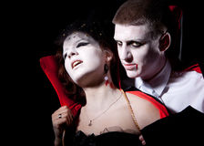 Vampire couple bite. A vampire biting a young woman from behind Stock Photography