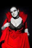 Vampire dans la robe rouge recherchant Photographie stock