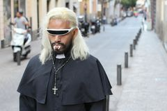 Vampire dressed like a priest walking outdoors royalty free stock photos