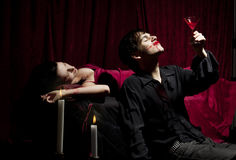 Vampire drink. Vampire enjoying his bloody drink. His dead prey is lying behind him Royalty Free Stock Image