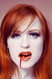 The vampire with fiery hair. Portrait of red hair woman vampire Royalty Free Stock Image