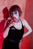 Vampire girl with glass of red blood drink Stock Photos
