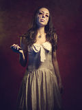 Vampire girl with a knife. Blood leaks from her eyes Royalty Free Stock Images