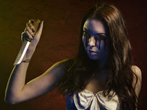Vampire girl with a knife. Blood leaks from her eyes Stock Images