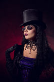 Vampire gothic girl in tophat and round eyeglasses. Studio shot with smoke background stock photo