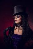 Vampire gothic girl in tophat and round eyeglasses. Studio shot with smoke background Stock Photo