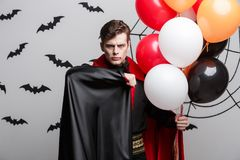 Portrait of handsome caucasian in Vampire halloween costume with colorful Balloon. Vampire Halloween Concept - Portrait of handsome caucasian in Vampire Royalty Free Stock Image