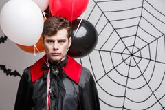 Portrait of handsome caucasian in Vampire halloween costume with colorful Balloon. Vampire Halloween Concept - Portrait of handsome caucasian in Vampire Stock Photos