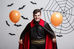Portrait of handsome caucasian in Vampire halloween costume with colorful Balloon. Vampire Halloween Concept - Portrait of handsome caucasian in Vampire Stock Image