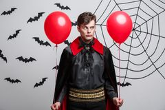 Portrait of handsome caucasian in Vampire halloween costume with colorful Balloon. Vampire Halloween Concept - Portrait of handsome caucasian in Vampire Royalty Free Stock Photo
