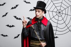 Vampire Halloween Concept - Portrait of handsome caucasian in Vampire halloween costume poining on side. Vampire Halloween Concept - Portrait of handsome Royalty Free Stock Photo
