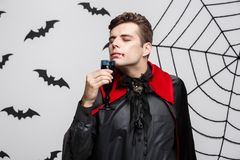 Vampire Halloween Concept - Portrait of handsome caucasian Vampire enjoy drinking bloody red wine. Vampire Halloween Concept - Portrait of handsome caucasian Royalty Free Stock Photos