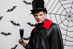 Vampire Halloween Concept - Portrait of handsome caucasian Vampire enjoy drinking bloody red wine. Vampire Halloween Concept - Portrait of handsome caucasian Stock Photo