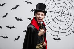 Vampire Halloween Concept - Portrait of handsome caucasian Vampire in black and red halloween costume singing with staff. Vampire Halloween Concept - Portrait of Royalty Free Stock Photos