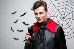 Vampire Halloween Concept - Portrait of handsome caucasian Vampire enjoy drinking bloody red wine. Vampire Halloween Concept - Portrait of handsome caucasian Royalty Free Stock Photography