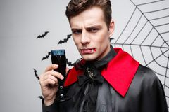 Vampire Halloween Concept - Portrait of Serious handsome caucasian Vampire enjoy drinking bloody red wine. Vampire Halloween Concept - Portrait of Serious Royalty Free Stock Images