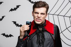 Vampire Halloween Concept - Portrait of Serious handsome caucasian Vampire enjoy drinking bloody red wine. Vampire Halloween Concept - Portrait of Serious Stock Photography