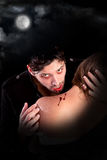 Vampire. Handsome vampire biting girl isolated in dark background Stock Image