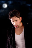 Vampire. Handsome vampire isolated in dark background Royalty Free Stock Photography