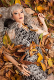 Vampire on leaves. Beautiful vampire woman lying on the ground on leaves, magic wand in hand Stock Photos