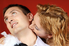 Vampire love. Young couple playing the role of female vampire biting her lover's neck Stock Image