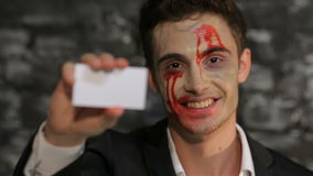 Vampire man shows a  business card. Vampire man shows a copyspace business card. Man in the image of the vampire posing on black background of a brick wall stock footage