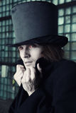 Vampire nation. Vampire man with bloody eyes in the black coat and top hat indoors. Natural makeup colors Stock Images