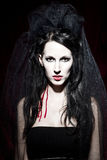 Vampire queen. Female newborn vampire, blood flowing down her neck. Very white due to the loss of much blood. She is wearing a black dress and a black veil Royalty Free Stock Images