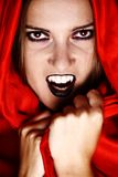 Vampire in red. Woman vampire showing her fang and covered in red Royalty Free Stock Images