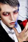 Vampire style. Portrait of a handsome young man with vampire style make-up. Shot in a studio stock image