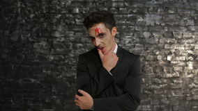 Vampire wipes away the blood. Male vampire wipes away the blood from his mouth. Man in the image of the vampire posing on black background of a brick wall stock video