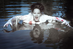 Vampire woman dressed white bloody shirt in the river Stock Photo