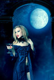 Vampire woman with glass of wine. Vampire woman in a dress looks at a glass of red wine Royalty Free Stock Photography