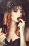 Vampire woman. Redhead vampire woman with glass of blood. Photo in vintage style Royalty Free Stock Images