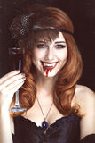 Vampire woman. Redhead vampire woman with glass of blood. Photo in vintage style royalty free stock photo