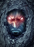 Vampire Zombie. Ghost with glowing evil eyes living inside a dark old haunted tree trunk as a halloween symbol of bad horror spirits haunting the living world stock illustration
