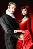 Vampires couple. Portrait of a beautiful couple in medieval costumes with vampire style make-up. Shot in a studio Stock Photos