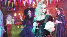 Vampiress satisface su gusto de la sangre en un partido de Halloween con un cráneo en sus manos almacen de metraje de vídeo