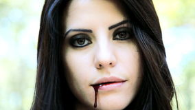 Vampiro fêmea que sorri com sangue na boca