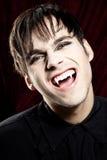 Vampiro maschio che sorride pericolosamente, mostrando le zanne fotografia stock