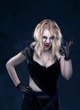 Vampiro rubio hermoso de la muchacha que lleva la ropa negra La sangre está en la boca y observa Foto de archivo libre de regalías