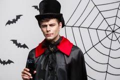 Vampirs-Halloween-Konzept - Porträt des ernsten hübschen kaukasischen Vampirs genießen, blutigen Rotwein zu trinken Lizenzfreie Stockfotos