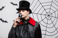 Vampirs-Halloween-Konzept - Porträt des hübschen kaukasischen Vampirs genießen, blutigen Rotwein zu trinken Stockbilder