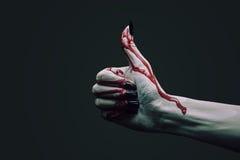 Vampyrhanden med tummen gör en gest upp Arkivfoton