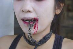 Vampyrkvinnor med kedjan i hennes mun Royaltyfri Foto