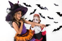 Vampyrtuggaarm av en häxa Allhelgonaaftonungar, lycklig läskig flicka och pojkeuppklädd i halloween dräkter av häxan och vampyren royaltyfri fotografi