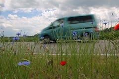 Van auf dem Weg, Landstraße mit roter Mohnblume und Mais blüht Lizenzfreie Stockbilder